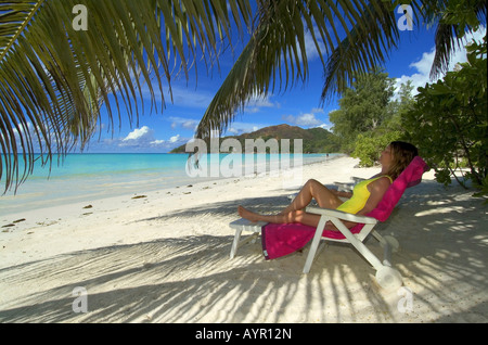 Young woman on deck chair, sleeping under palm trees, Praslin Island, Seychelles, Africa - Stock Photo