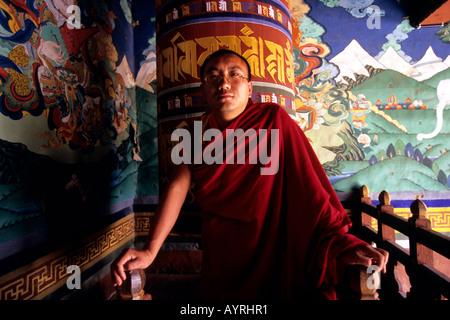 Buddhist monk with the prayer wheel behind, Bhutan - Stock Photo