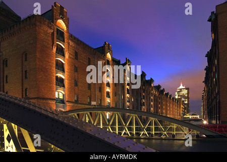 Historic storehouses in the Speicherstadt warehouse district of Hamburg at night and the modern Hanseatic Trade - Stock Photo