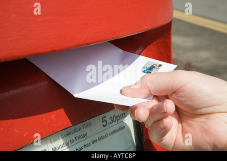 Close-up of person's hand holding posting a letter with 2nd class stamp to post in a red postbox. England UK - Stock Photo