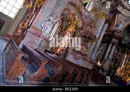 Horizontal wide angle perspective of the old wooden pews inside St.Nicholas Church 'Chram sv Mikulase' in Mala Strana. - Stock Photo