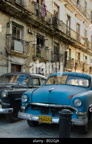 Street in the old town area of Havana, Cuba, featuring a couple of vintage cars. - Stock Photo