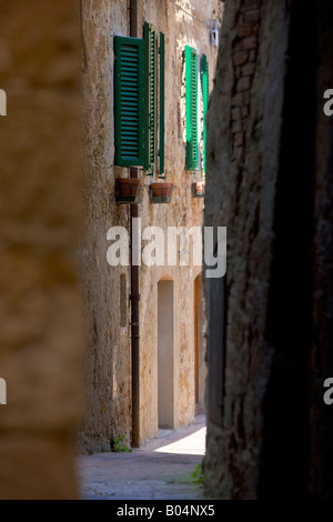 Narrow lane between old stone houses in the historic old town centre of Pienza, a UNESCO World Heritage Site - Stock Photo
