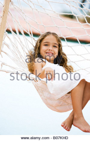 little girl sitting in a hammock smiling - Stock Photo