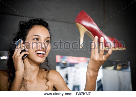 Woman buying high-heeled shoes in a shoe shop, talking on mobile phone - Stock Photo
