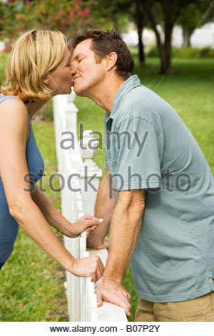 couple kissing standing either side of fence - Stock Photo