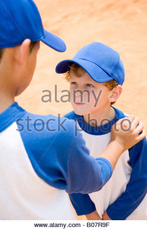 older boy talking down to younger boy at baseball practice - Stock Photo