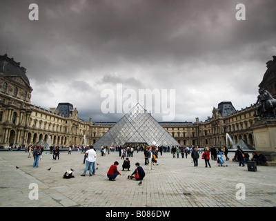Louvre courtyard with many people tourists and the pyramid by I M Pei Paris France - Stock Photo