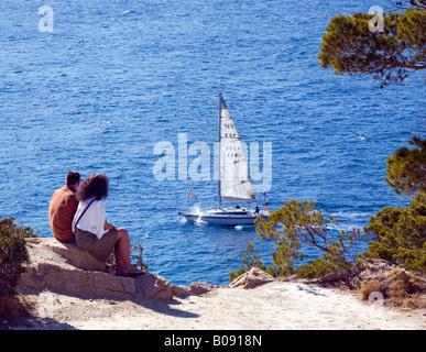 Couple sitting on the edge of a steep coast watching a sailboat near Sant Elm, Majorca, Balearic Islands, Spain - Stock Photo