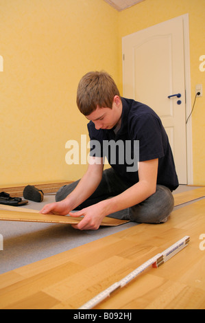 Teenager laying parquet flooring - Stock Photo