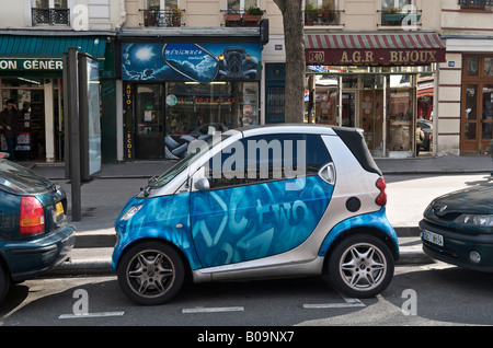 Smart car parked in small space in a Paris street - Stock Photo