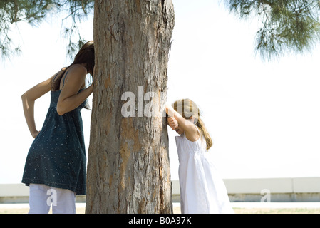 Two sisters playing hide-and-seek, one peeking around tree as the other counts - Stock Photo