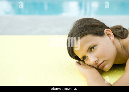 Teenage girl lying on stomach, head resting on arms, looking away - Stock Photo