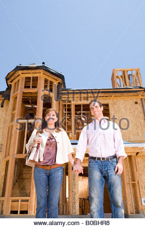 Young couple holding hands in front of partially built house, low angle view - Stock Photo