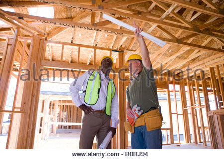 Builder in hardhat pointing up to businessman in partially built house, low angle view - Stock Photo