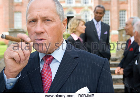 Businessman with cigar by manor house, colleagues in background, portrait - Stock Photo