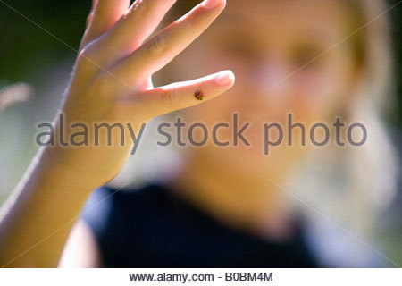 Girl  with ladybird on finger, close-up of hand - Stock Photo