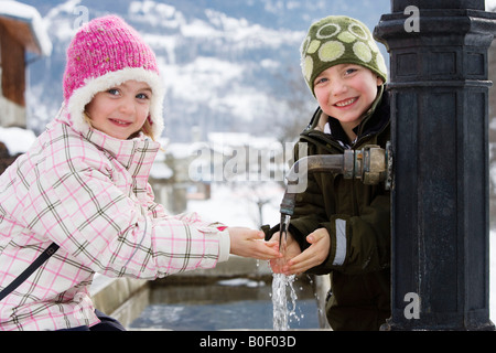 Boy and girl holding hands under tap - Stock Photo