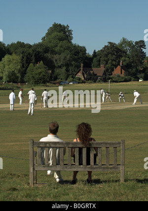 couple on bench watching english village cricket - Stock Photo