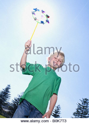 Young boy outdoors holding windmill and smiling - Stock Photo