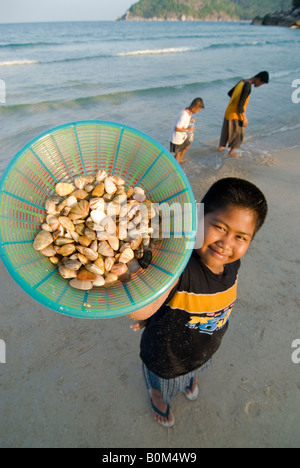 Local Asian village boys show their morning's work of collecting shells and clams on a beach in southern Thailand. - Stock Photo