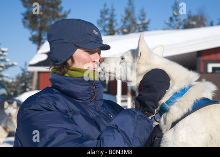 A woman and a husky, nose to nose in winterly Lapland / northern Sweden - Stock Photo