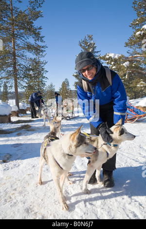 A woman strokes a husky at a dogsledge ride with siberian huskies in winterly Lapland / northern Sweden - Stock Photo