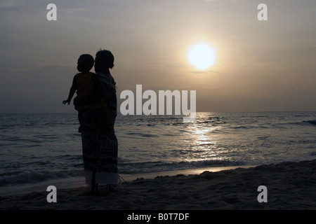 Woman with child staring at the sea at sunset - Stock Photo