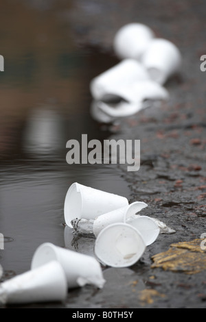 discarded polystyrene styrofoam cups lying by a puddle in the road - Stock Photo