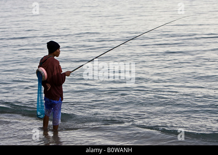 Fisherman fishing in the rain on the shore of Lombok Island, Lesser Sunda Islands, Indonesia - Stock Photo