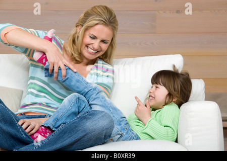 Mother and daughter (6-7) sitting on sofa, portrait - Stock Photo