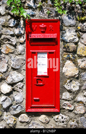 Red Victorian post box on stone wall, Wimborne Minster, Dorset, England, United Kingdom - Stock Photo
