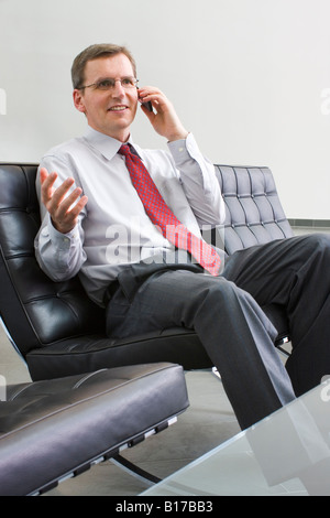 Businessman or politician talking on cell phone while sitting in a chair of leather - Stock Photo
