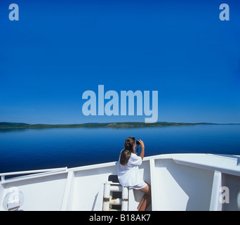 Young girl Birdwatching on deck of Coastal Boat, Cartwright, Labrador, canada - Stock Photo