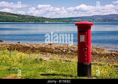 A red Royal Mail pillar box standing on the shoreline at Port Bannatyne, Isle of Bute, Argyll & Bute, Scotland. - Stock Photo