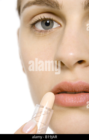 Young woman applying lipstick, cropped view - Stock Photo