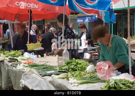 Rijeka Croatia Europe Outdoor street market stall woman stallholder selling fresh vegetables - Stock Photo