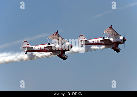 Two Boeing Stearman biplanes from Team Guinot perform their wingwalking feats at the Biggin Hill Airshow - Stock Photo