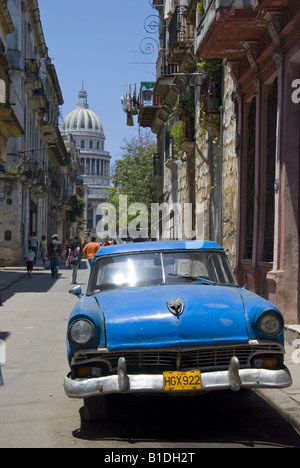 Classic car in old street of Havana, Cuba, with Capitol in the background - Stock Photo