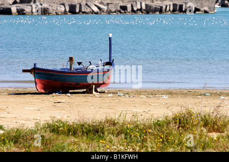 Old wooden fishing boat on Catania beach on Sicily, Italy - Stock Photo