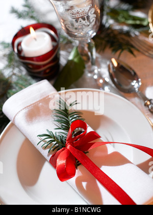 White napkin decorated with a fir branch and a red ribbon - Stock Photo