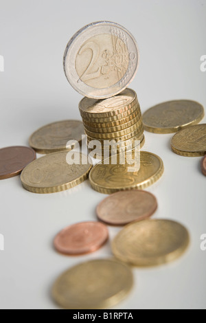 Stacked Euro coins and other coins lying on a table - Stock Photo