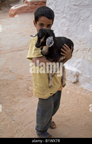 Young Morocan Touareg shepherd boy carrying young goat .89276_Morocco - Stock Photo