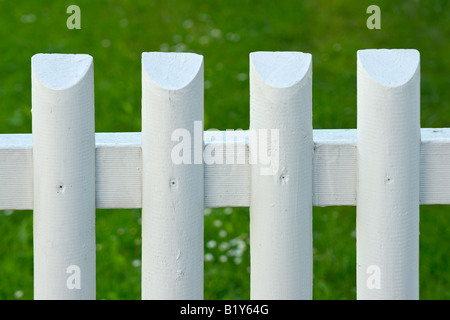 White batten garden fence with green grass on background - Stock Photo