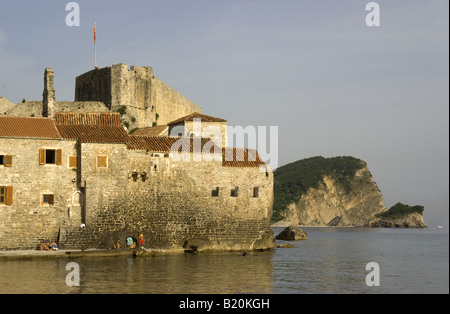 Budva Old Town fort and walls with bathers on Adriatic coast of Montenegro - Stock Photo