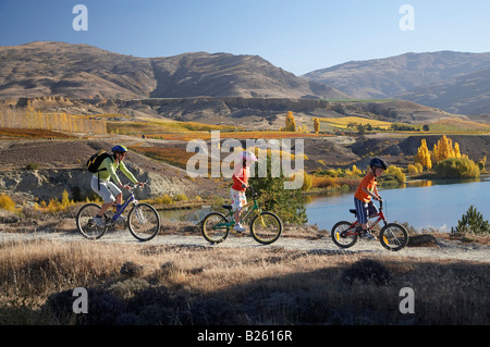 Mountain Bikers Lake Dunstan and Autumn Colours Bannockburn Central Otago South Island New Zealand - Stock Photo