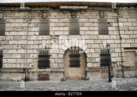Old building with iron bars on the window, showing damage from bullet holes from World War 2 - Stock Photo