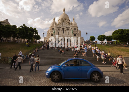 Blue Volkswagen beetle passing in front of crowded steps leading to Sacre Coeur Cathedral in the Montmartre area, - Stock Photo