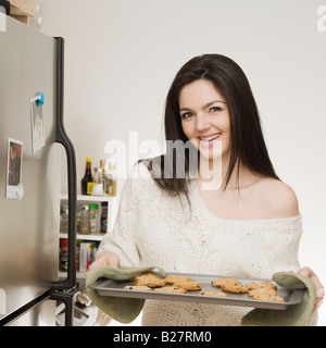 Woman holding tray of cookies - Stock Photo