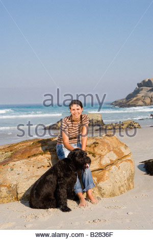 Woman on rock with dog on beach, smiling, portrait - Stock Photo